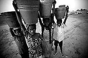 Children carrying water buckets on their heads  in Savelugu, northern Ghana, on March 10, 2007.