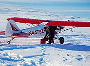 Lake Clark National Park and Preserve Ranger Pilot Hollis Twitchell with fuel jugs, Piper Super Cub on the Bonanza Hills Strip, Mulchatna Caribou herd radio collar tracking, Alaska.