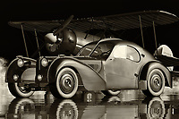 """The Bugatti 1957-SC Atlantic is one of the most desirable and successful of the many models that comprise the Vintage Class types of Bugatti cars. Constructed from the body of the last restored Bugere Type 37 and using a body style that Bugatti calls """"Aqua,"""" the car borrows its styling from the Type 38 Grand Prix race car. The most important part of this restoration was the use of a high-performance fiberglass body, which ensured that the natural lines of the old car were retained, even though the bodywork had been significantly updated. In keeping with the original design, the most striking feature of this restored car is the two large air ducts located behind the front wheels.<br /> <br /> Designed to maximize down force and drag, the new air dam system can be seen from all angles and helps to increase down force by decelerating the car's overall speed. Because of the extra drag created by the air dam, the engine starts to slow down, which in turn lowers the center of gravity of the car and improves handling on the straights. This air-flow separation also helps the designers to achieve a higher top speed by allowing additional energy to be directed into the drive system.<br /> <br /> Bugatti designed the 1957-SC Atlantic with a number of advanced features that make it different from most sports cars at the time. High profile Brembo brakes are paired with a four-wheel drive that utilizes a special magnesium-alloy rotary damper that works to reduce lift by channeling cooling air through the blockages. A combination of Brembo and magnesium makes these brakes effective on surfaces like asphalt and concrete, while the result is fluid and heat dissipation, allowing the brakes to remain open during a high-speed corner. The side skirts, air vents, and a rear diffuser further improve high-speed driving, as well as added down force. Finally, Bugatti designed and built the suspension to work with the air flow and provide optimal handling."""