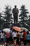 Visitors at the Statue Square near Mao's birthplace in Shaoshan, Hunan Province, China on 12 August 2009.  The village of Shaoshan, in rural Hunan Province, is tiny in size but big in name. It was the childhood home for Mao Zedong, the controversial revolutionary who came from obscurity but eventually defied all odds conquered China in the name of communism. Now his home, a sacred place among China's official propaganda, is in reality a microcosm of the country itself: part commercialism, part superstition, with a dash of communist ideological flavor.