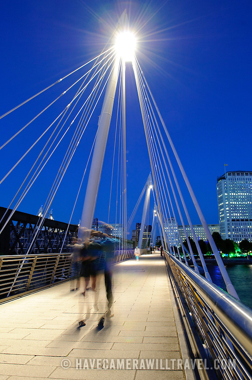 Hungerford Bridge between Embankment and Waterloo with motion blur of tourists walking.