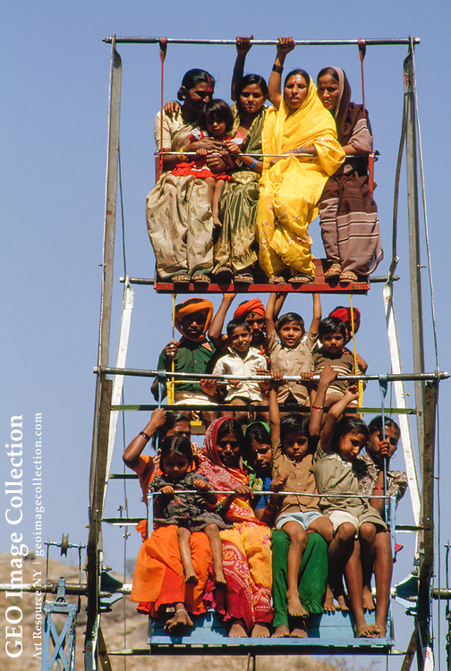 """View of tribal Indians wearing their best festival clothing--colorful dresses a nd silver jewelry--riding what appears to be a ferris wheel.  This photograph w as taken during the """"Bhil"""" tribal celebration of """"Bhagoriya"""" on the day of Holi . According to the photographer, this is the largest festival celebrated by the Bhil tribal peoples.  During this festival, Bhil tribals perform """"warrior dances"""" in the s treet. They use sugarcane stalks in the place of swords, which are now banned b y the p olice.  The photographer says many of the men had been drinking.  One of the tr aditions of this festival is for girls to grab young men, sing to them, and for ce them to pay a few coins before they are released.  This girl appears to be w earing a Hindu Ca ste mark.  DATE OF PHOTOGRAPH:  3/3/88."""