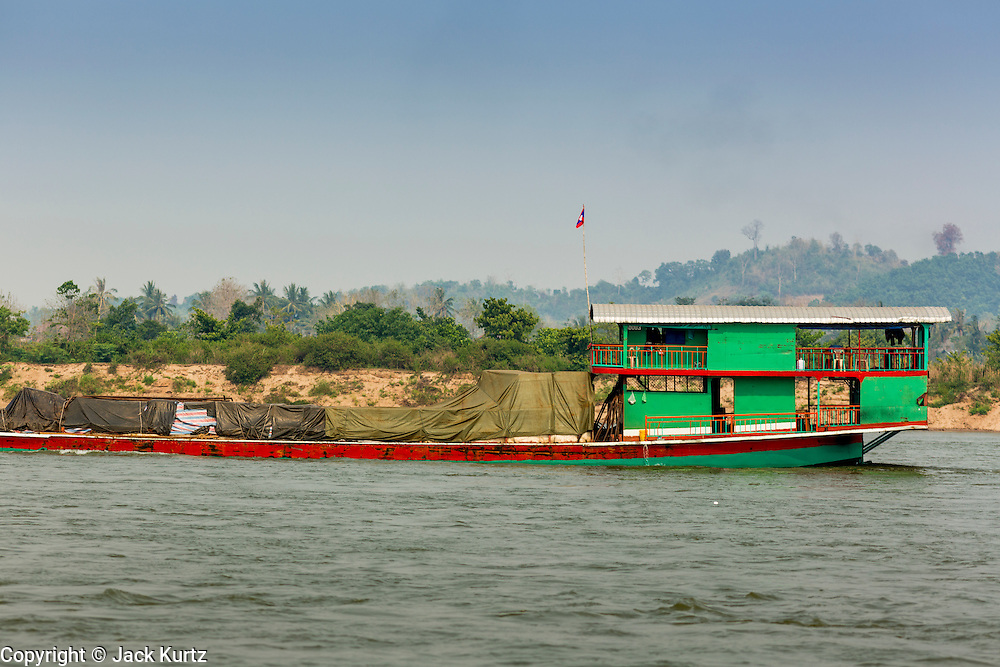 21 APRIL 2014 - CHIANG SAEN, CHIANG RAI, THAILAND: A Laotian flagged river freighter takes Thai made computer parts upriver to China through Chiang Saen, Thailand. Chiang Rai province in northern Thailand is facing a drought this year. The 2014 drought has been brought on by lower than normal dry season rains. At the same time, closing dams in Yunnan province of China has caused the level of the Mekong River to drop suddenly exposing rocks and sandbars in the normally navigable Mekong River. Changes in the Mekong's levels means commercial shipping can't progress past Chiang Saen. Dozens of ships are tied up in the port area along the city's waterfront.      PHOTO BY JACK KURTZ