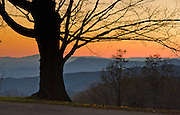 The orange sun sets in Shenandoah National Park along Skyline Drive, a National Scenic Byway in the Blue Ridge Mountains of Virginia, USA. Skyline Drive travels 105 miles (169 km) along the ridge of this long and narrow national park, with the broad Shenandoah River and valley on the west side, and the rolling hills of the Virginia Piedmont on the east. Shenandoah NP was authorized in 1926 and fully established on December 26, 1935. Almost 40% of its land has been designated as Wilderness, protected as part of the National Wilderness Preservation System.