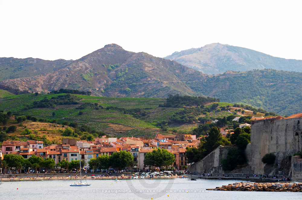 The beach in the village. The chateau in Collioure harbour. Collioure. Roussillon. France. Europe. Mountains in the background.