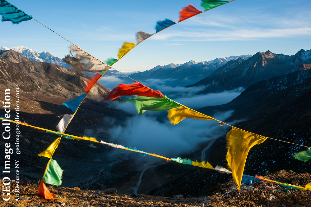 Prayer flags, placed by pilgrims to ensure safe travel, wave over Zheduo Pass, high above the mist-filled valley. Sichuan, China