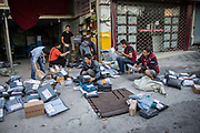 Couriers sort through packages for delivery at a distribution station in Shanghai, China, on Friday, Oct. 2, 2015.