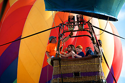 """Day 2, Festival of Ballooning. Solberg-Hunterdon Airport, Readington Township, NJ - July 28, 2013; <br /> <br /> Passengers take part in a tethered hot air balloon flight at the 2013 annual QuikChek New Jersey Festival of Ballooning in Readington, NJ.<br /> <br /> - - -<br /> <br /> """"While New Jerseyans may be stronger than any storm, hot air balloons are delicate aircraft, vulnerable to the elements."""" <br /> <br /> A selection of photos in this collection are published with the July 29 article by Jana Shea on WHYY's NewsWorks.org: <br /> N.J. Balloon Festival was a barometer for the weekend's wild weather.<br /> <br /> Read the article here: http://www.newsworks.org/index.php/new-jersey-more/item/57845-nj-balloon-festival-a-barometer-for-weekends-wild-weather"""