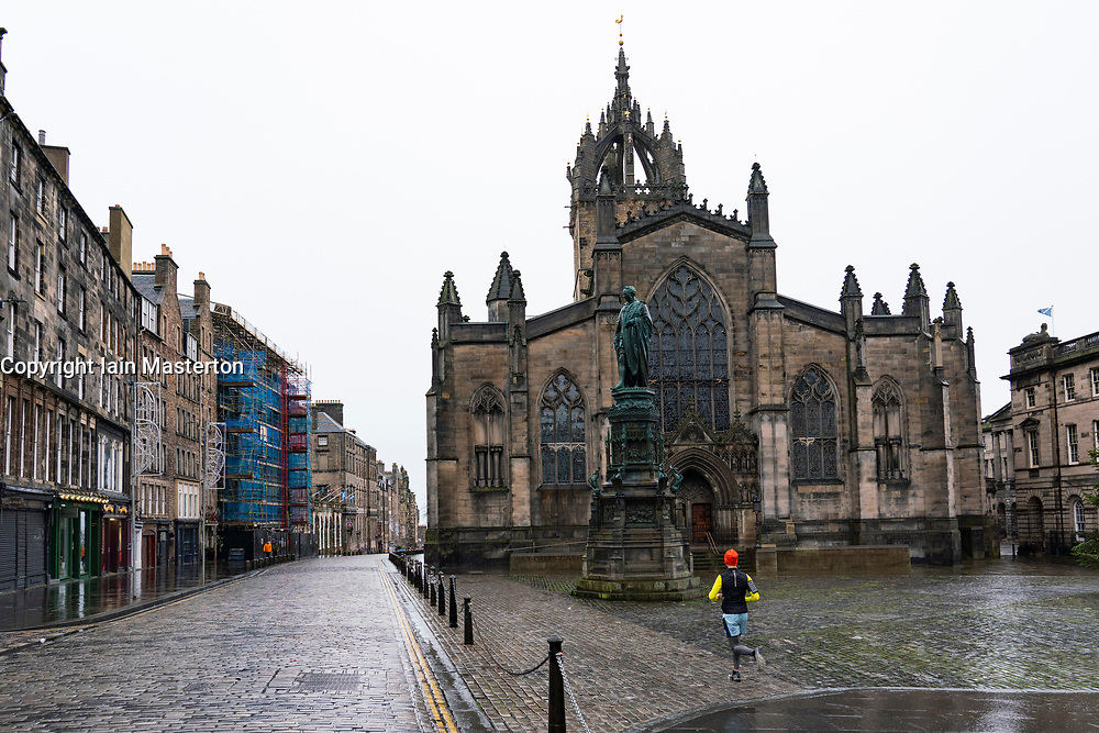 Edinburgh, Scotland, UK. 26 December 2020. Scenes from Edinburgh City Centre on a wet and windy Boxing Day during storm Bella. Today is first day that Scotland is under level 4 lockdown and all non essential shops and businesses are closed. As a result the streets are almost deserted with very few people venturing outside. Pic; The Royal Mile at Lawnmarket is almost deserted of people.  Iain Masterton/Alamy Live News