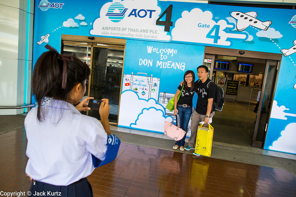 01 OCTOBER 2012 - BANGKOK, THAILAND:  Hostesses take passengers' photos as they walk into Don Mueang International Airport in Bangkok. Don Mueang International Airport is the smaller of two international airports serving Bangkok, Thailand. Suvarnabhumi Airport, opened in 2006 is the main one. Don Mueang was officially opened as a Royal Thai Air Force base on 27 March 1914 and commercial flights began in 1924. Don Mueang Airport closed in 2006 following the opening of Bangkok's new Suvarnabhumi Airport, and reopened as a domestic terminal for low cost airlines after renovation on 24 March 2007. Closed during the flooding in 2011, Don Mueang was again renovated and reopened in 2012 as the airport for low cost airlines serving both domestic and international passengers. On Monday, Air Asia, Asia's leading low cost airline, transferred all of their flight operations to Don Mueang and the airport was officially reopened. Suvarnabhumi International Airport is already over capacity and Don Mueang's importance as a hub is expected to grow.   PHOTO BY JACK KURTZ