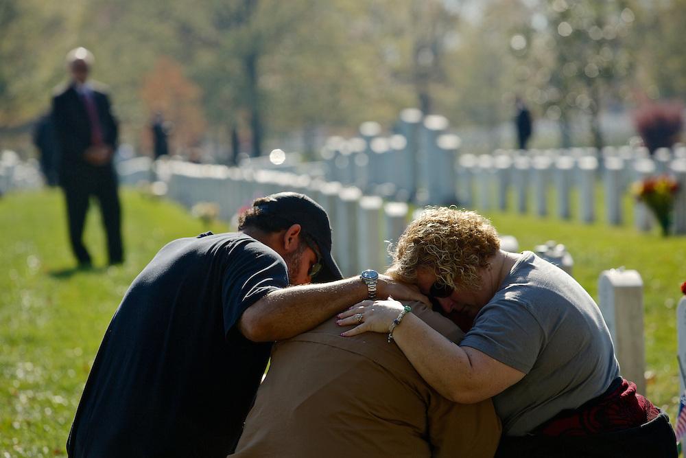 ARLINGTON, VA - NOVEMBER 11: Chuck Jackson (L) and Kimberly Shrauger (R) comfort Kimberly's husband Lowell Shrauger as he visits the grave of his life-long friend, Staff Sgt. Jamie L. Huggins, on Veteran's Day at Arlington National Cemetery on November 11, 2012 in Arlington, Virginia.