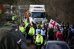 © Licensed to London News Pictures . 21/03/2014 . Barton Moss , Manchester , UK . Protesters march along Barton Moss Road slowly , in front of lorries leaving the iGas site .  The Barton Moss anti-fracking demonstration camp today (Friday 21st March 2014) . Photo credit : Joel Goodman/LNP