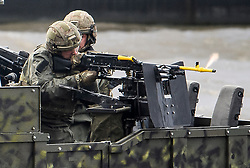 © Licensed to London News Pictures. 24/10/2018. London, UK. Armed Marines fire a machine gun from the back of a boat during the exercise. British Royal Marines are joined by the The Royal Netherlands Marines in a military demonstration at HNLMS Zeeland, which is anchored next to anchored next to HMS Belfast on the River Thames in central London. Members of the British and Dutch Royal families watched the event as part of a state visit to the UK. Photo credit: Ben Cawthra/LNP