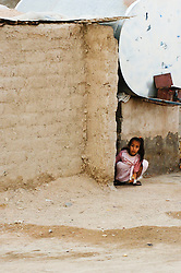 A Young Iraqi girl looks out from her roughly built home as a British Army patrol of Royal Dragoon Guards passes through Umm Qasr town Southern Iraq, while on Op-Telic in March 2005