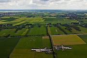 Nederland, Overijssel, Gemeente Twenterand, 30-06-2011; Landschap ten noorden Vriezenveen, links Vroomshoop, rechts esterhaar-Vriezeenveenswijk. Voorbeeld van vroege ruilverkaveling (jaren '50). De oorspronkelijk (zeer) smalle en lange kavels, ontstaan door het ontginnen van veen, zijn samengevoegd tot grotere blokken en veelal is het kavelpatroon 90 graden gedraaid. De globale oorspronkelijke - onderliggende - structuur is deels nog herkenbaar..Naast de gedraaide verkalveling zijn verder kenmerkend de 'boerderijstraten', linten van boerderijen omgeven door singels van bomen (diagonaal in het midden)..Landscape north of Vriezenveen, an early example of land consolidation (50s)..The original (very) long and narrow lots, created by the extraction of peat, are merged into larger blocks and in most cases the plot pattern has been rotated 90 degrees  The original - underlying - structure is still partly visible..Further characteristic features are the 'farm roads' with farmhouses surrounded by belts of trees..luchtfoto (toeslag), aerial photo (additional fee required).copyright foto/photo Siebe Swart