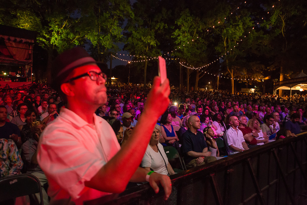 A man in the audience taking a photo of Esperanza Spalding's performance at Celebrate Brooklyn. Behind him is a small part of the audience.