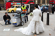 A council street sweeper from Westminster Council walks through a Chinese wedding photo shoot in London, causing the photographer to stop shooting