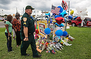 A makeshift memorial grows in front of the B-quick store on Airline in Baton Rouge where officers were killed on Sunday.