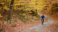 Man mountain biking on a Vermont country road during peak fall color.
