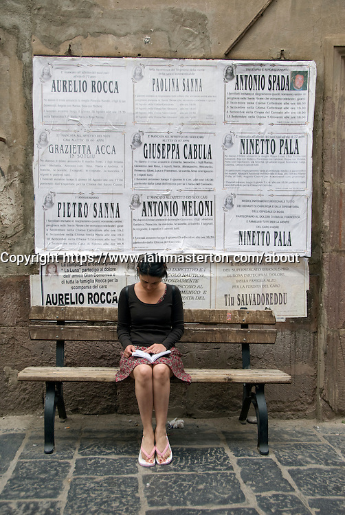 Woman sitting reading beneath old posters in village of Bosa in Sardinia Italy