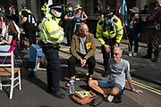 Metropolitan Police officers ask environmental activists from Extinction Rebellion to move out of a road in the Covent Garden area during the first day of Impossible Rebellion protests on 23rd August 2021 in London, United Kingdom. Extinction Rebellion are calling on the UK government to cease all new fossil fuel investment with immediate effect.