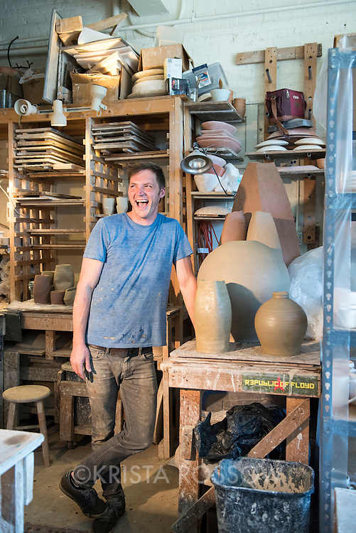 Josh Copus (model released) at work in his studio throwing pots out of harvested North Carolina wild clay. The Clayspace Co-op is a cooperative of professional ceramic artists located at the Wedge Studios at 119 Roberts Street in the River Arts District of Asheville, North Carolina.