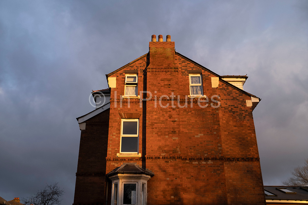 Red brick end house in Moseley in evening light on 9th February 2021 in Birmingham, United Kingdom. Moseley is an area where individual and grand homes were built by industrialists in the early 1900s. Moseley and the surrounding areas were much developed after 1910, the new properties being mostly of large houses, designed to cater for the Edwardian middle-class families that settled in the suburbs surrounding Birminghams industrial centre.