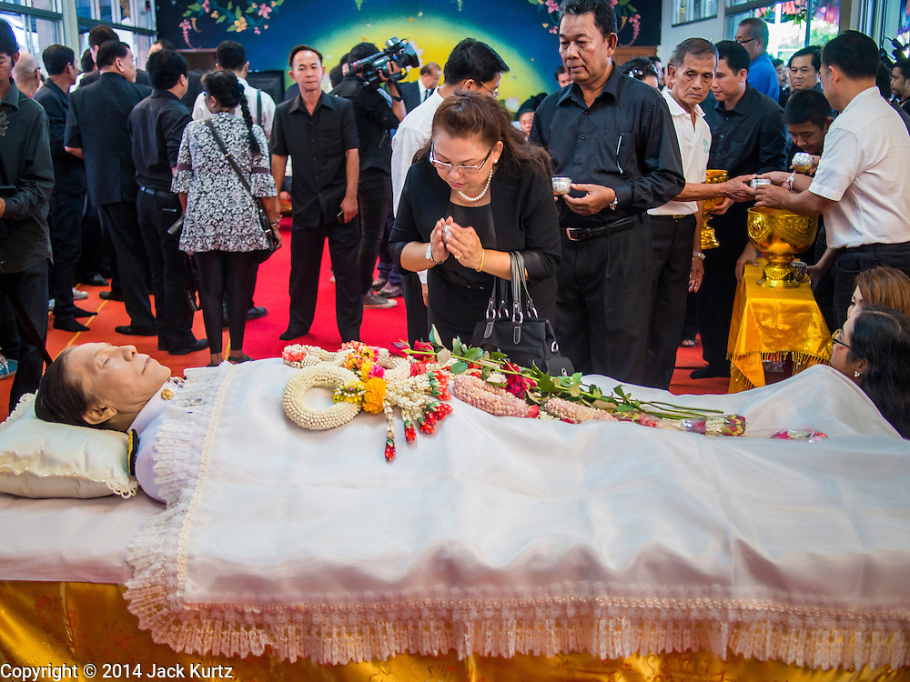 12 OCTOBER 2104 - BANG BUA THONG, NONTHABURI, THAILAND: People pay respects to Apiwan Wiriyachai, whose funeral rites started at Wat Bang Phia, in Bang Bua Thong, a Bangkok suburb, Sunday. Apiwan was a prominent Red Shirt leader, member of the Pheu Thai Party of former Prime Minister Yingluck Shinawatra, and a member of the Thai parliament. The military government that deposed the elected government in May, 2014, charged Apiwan with Lese Majeste for allegedly insulting the Thai Monarchy. Rather than face the charges, Apiwan fled Thailand to the Philippines. He died of a lung infection in the Philippines on Oct. 6. The military government gave his family permission to bring him back to Thailand for the funeral. He will be cremated later in October. The first day of the funeral rites Sunday drew tens of thousands of Red Shirts and their supporters, in the first Red Shirt gathering since the coup.    PHOTO BY JACK KURTZ