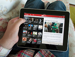 Man reading digital app edition of BBC News on an iPad touch screen tablet computer