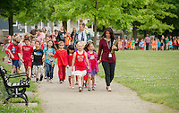 Elm Street students Keira Stevens and Mayah Maheu lead their classmates around Leavitt Park with first grade Teacher Alison Davis during the WALK NH program on Thursday morning.  (Karen Bobotas/for the Laconia Daily Sun)