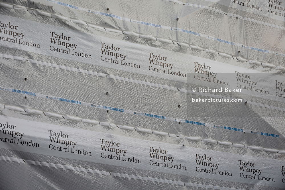 "Detail of construction sheeting by Greater London Demolition on a site being cleared for the 10-storey luxury apartment development called The Denizen, a controversial building by Taylor Wimpey on Golden Lane that locals say will dominate their view and block their daylight, on 30th October 2017, in London, England. Despite this, they say ""We are one of the UK's largest residential developers. As a responsible developer we are committed to working with local people and communities."""
