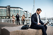 Businessman working on a laptop, sat outside at the waterfront and marina at Castle Quay, St Helier, Jersey