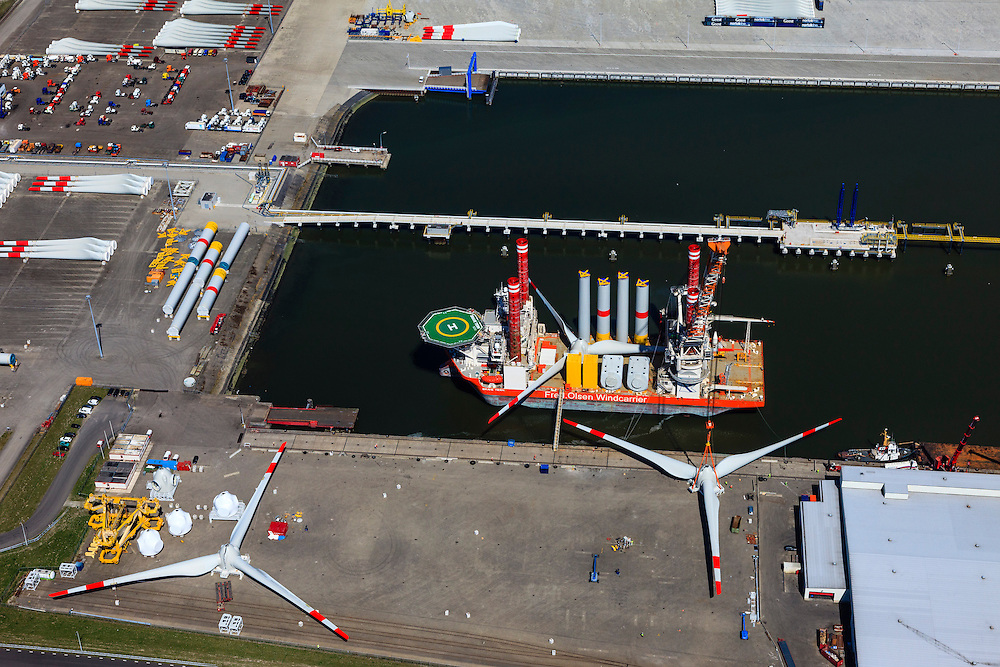 Nederland, Groningen, Eemshaven, 01-05-2013; de Julianahaven, opslag en assemblage van onderdelen van offshore windturbines, zoals wieken (rotorbladen), masten, turbines. Op de  windcarrier met helikopterdek de onderdelen van windmolens. Een hijskraan hijst een gemonteerd  wiekenblok omhoog..De firma Fred. Olsen Windcarrier is verantwoordelijk voor transport, installatie en onderhoud van offshore wind parken..Port of Eemshaven: storage and assembly of components for offshore wind turbines in the Julianahaven at Eemshaven. .Fred. Olsen Windcarrier company provides innovative and tailored services for the transport, installation, and maintenance of offshore wind parks, such as wings (blades), masts, turbines. On the wind carrier with helicopter deck the parts of a windmill. A crane lifts mounted wings..luchtfoto (toeslag op standard tarieven).aerial photo (additional fee required).copyright foto/photo Siebe Swart