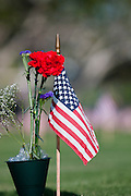 An American Flag and a flower sit on the rave of a soldier at Punchbowl National Cemetery of the Pacific on Memorial Day.