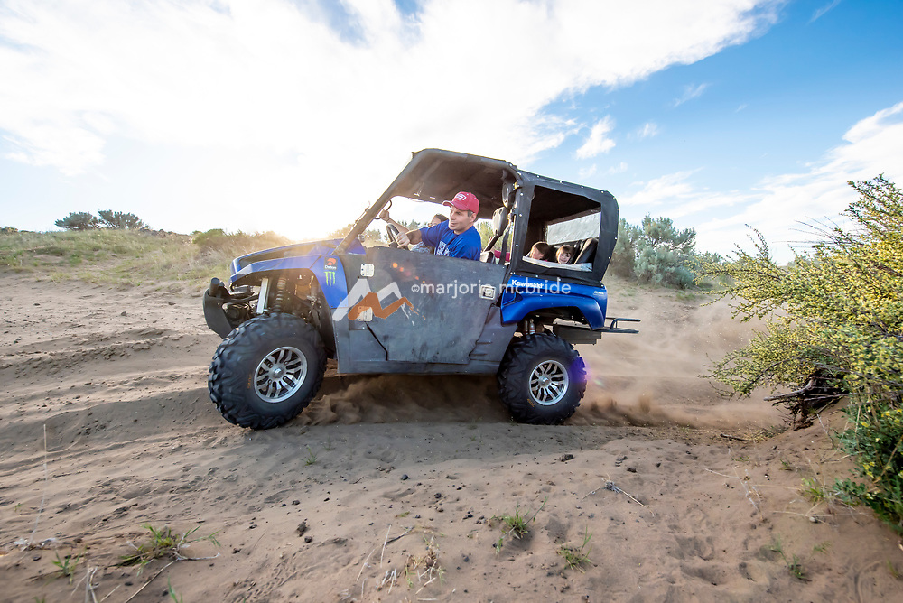 Family kicking up the dirt while enjoying ATV ride throught desert and deep sage during spring in Wendell, Idaho. MR