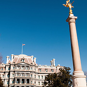 The Eisenhower Executive Office Building (also known as the Old Executive Office Building) next to the White House in downtown Washington DC. The building provides office space for many White House staffers and other government workers. In front of the building is the First Division Monument commemorating First Division of the American Expeditionary Forces who gave their lives during World War I. At its top is a gilded bronze statue of Victory.