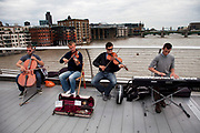 String quartet buskers perform to passers by on Millennium Bridge over the River Thames. A busy thoroughfare between St Paul's and Bankside this is a key spot to catch both tourists and locals alike. The band drew a good crowd and made for a unique busking sound.