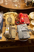 Old telephones on display in house clearance auction sale room, UK