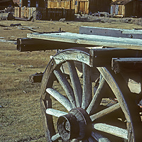 A vintage wagons is parked in front of old buildings at Bodie Ghost Town State Park in Mono County, California.