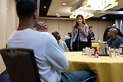 UConn President Susan Herbst speaks with head coach Kevin Ollie during the team lunch at the Hyatt Regency in Dallas, Texas before watching her school compete in the NCAA Final Four on April 5, 2014. (Cooper Neill / for The New York Times)