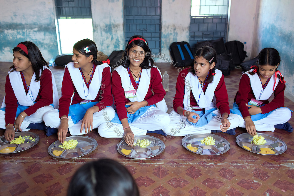 Ritu Gaur, 13, (centre) is smiling while consuming a meal inside the MS Jamoniya Tank Schhol, near Sehore, Madhya Pradesh, India. Ritu lives in the adjacent Jamoniya Tank Girls Hostel, where the Unicef India Sport For Development Project has started in 2012. Covering 313 state-run girls' hostels and 207 mixed hostels in Madhya Pradesh, the project ensures that children from Scheduled Tribes (ST) and others amongst the poorest people in India, can easily access education and be introduced to sports. Field workers from Unicef also oversee their nutrition and monitor the overall conditions of each pupil.