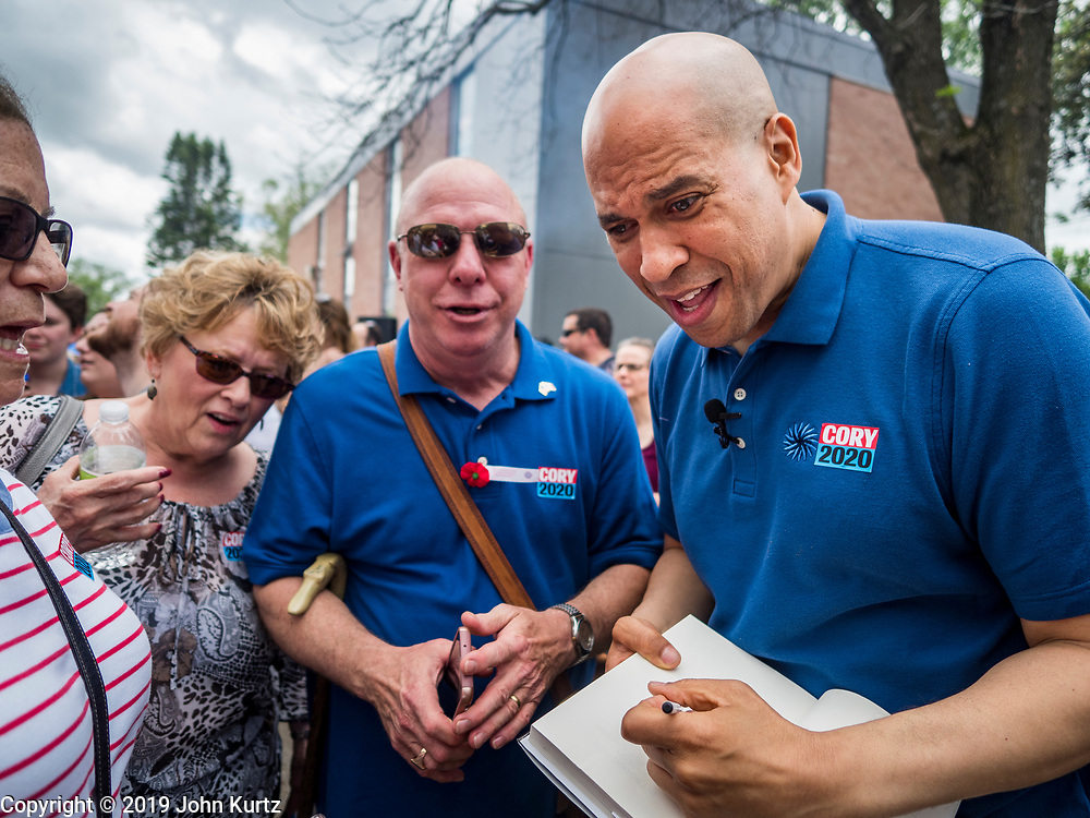 27 MAY 2019 - URBANDALE, IOWA: US Senator CORY BOOKER (D-NJ) signs a book at a Memorial Day barbecue he hosted at his Iowa campaign headquarters. Sen. Booker is running to be the Democratic nominee for the US Presidency. Iowa traditionally hosts the the first selection event of the presidential election cycle. The Iowa Caucuses will be on Feb. 3, 2020.                PHOTO BY JACK KURTZ