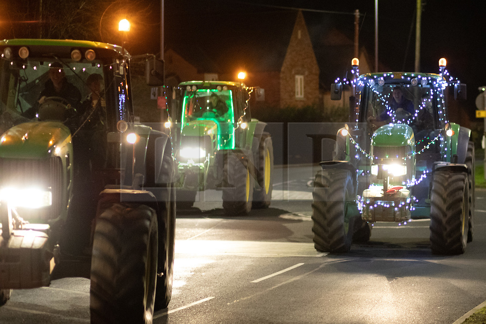 © Licensed to London News Pictures. 14/12/2019. Twycross, Leicestershire, UK. Farmers from around North Warwickshire and Leicestershire decorated their tractors and took part in a run around country villages to raise money for charity. The inaugural run started in Sheepy Magna, through Orton on the Hill, Austry, Twycross, Ratcliffe Culey, finishing in the market square, Atherstone. Thirty tractors took part with the farmers tooting at onlookers as they drove past spreading Christmas cheer around the countryside. Photo credit: Dave Warren / LNP