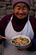 A woman eating noodles Lang Zhong, Sichuan Province, China