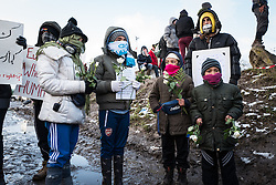 © London News Pictures. Calais, France. 07/03/16. Refugee children carry white flowers, which they tried to give to French riot police in an attempt to halt the demolition. French authorities are evicting and demolishing the southern half of the Calais 'Jungle' camp, which charities estimate to contain 3,500 people. . Photo credit: Rob Pinney/LNP