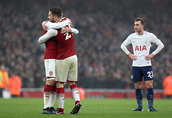 Arsenal's Nacho Monreal (left) and Shkodran Mustafi celebrate victory as Tottenham Hotspur's Christian Eriksen stands dejected at full time of the Premier League match at the Emirates Stadium, London.