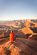 Tourist sat on rock overlooking Dead Horse Point, Arches National Park, Utah, United States of America