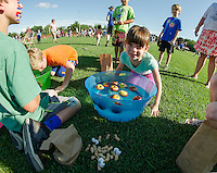 Hannah Thornsbury and Connor Jacques bob for apples during the Peanut Festival with the Opechee Day Camp on Thursday evening.  (Karen Bobotas/for the Laconia Daily Sun)