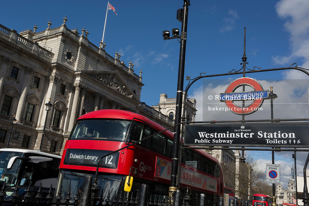 With Union Jack flags flying from the roof of government buildings, a number 12 Go Ahead London bus to Dulwich Library passes-by one of the entrances to Westminster Underground station and public subway, on the south side of Whitehall, on 11th March 2020, in London, England.