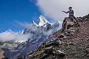 Day 3 of 10: From Alto de Pucaraju pass (15,300 ft or 4640 m), a trekker points to Nevado Taulliraju (19,100 ft or 5830 m). Trek 10 days around Alpamayo, in Huascaran National Park (UNESCO World Heritage Site), Cordillera Blanca, Andes Mountains, Peru, South America. For licensing options, please inquire.